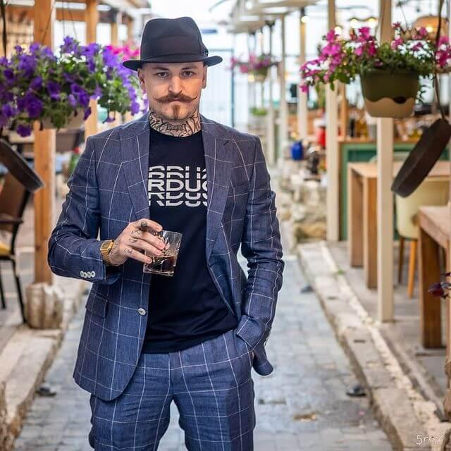 Мъж със син костюм, пура, шапка и чаша с уиски.
